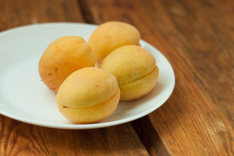 Fruits frais mûrs d'abricot d'un plat blanc sur le fond en bois L'espace de copie, nourriture saine delisious photographie stock libre de droits