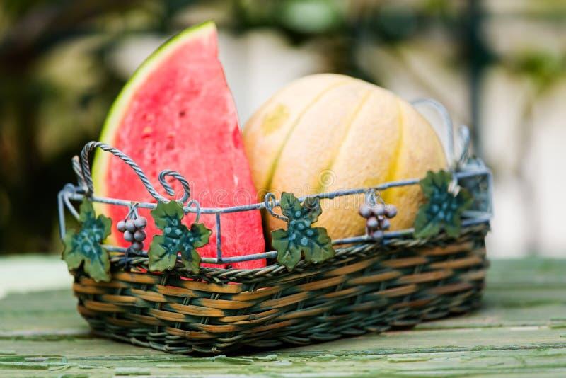 Fruits frais, pastèque et rockmelon saisonniers dans le panier sur le dessus de table, extérieur photographie stock libre de droits