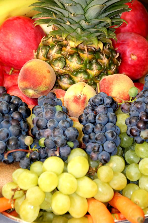 Fruits. Fruit tower with pineapple, grapes, peaches and apples royalty free stock image