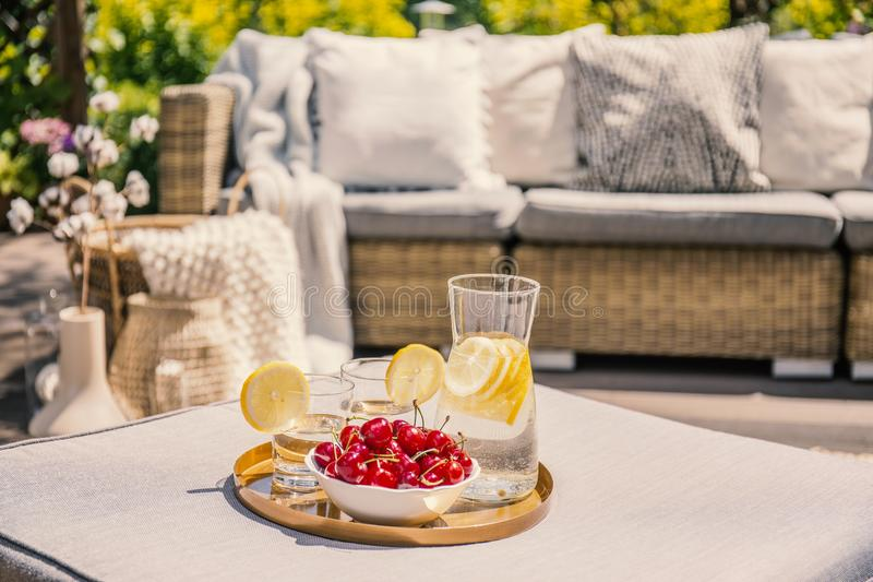 Fruits and glass with water on rattan table on the terrace with royalty free stock photo