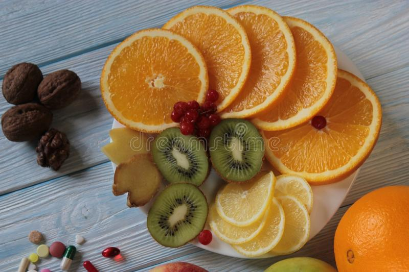 Fruits lie on a plate-kiwi, oranges, pomegranate and pills. royalty free stock photo