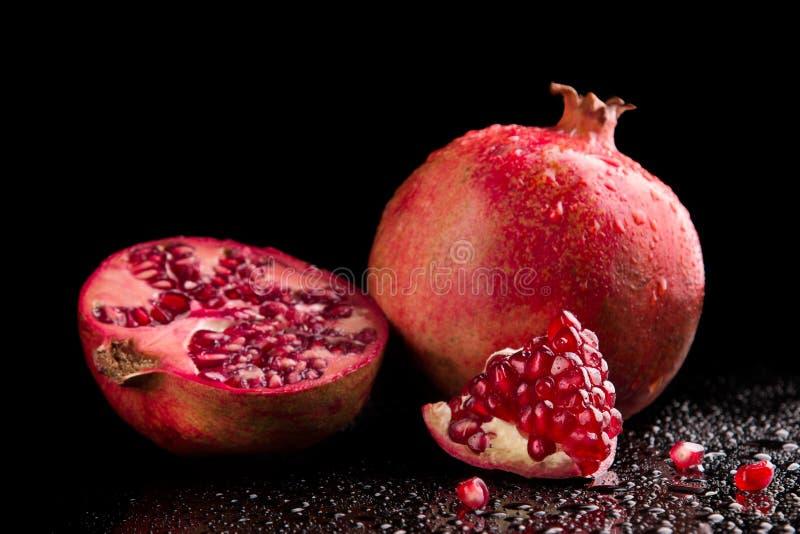 Fruits mûrs de grenade sur un fond noir images stock