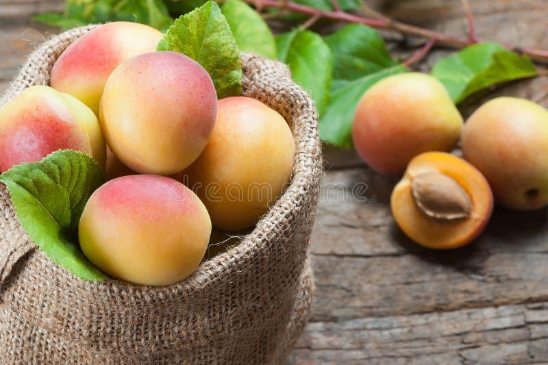 Fruits mûrs entiers frais d'abricot avec une feuille et moitié dans le sac à toile de jute sur la table rustique en bois images stock