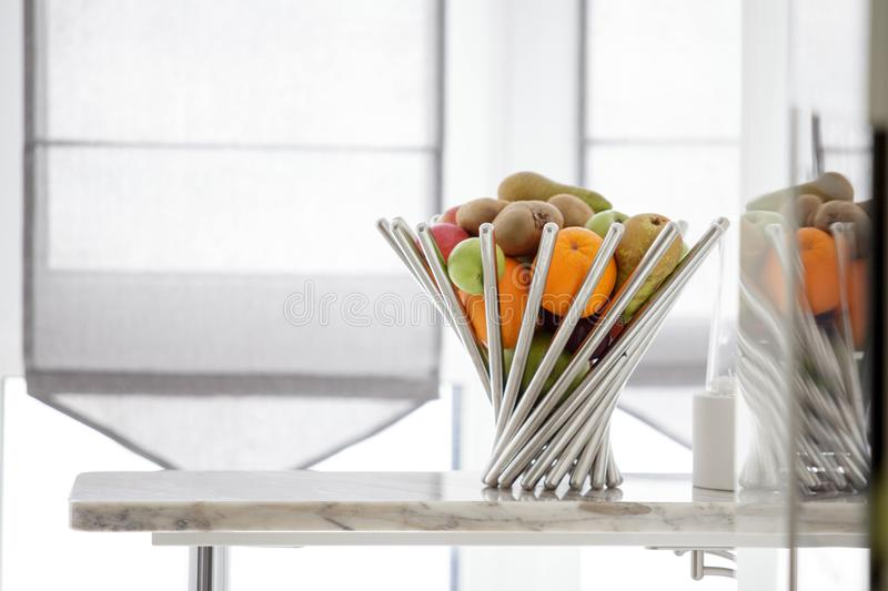 Fruits in the metal vase on table, fresh pomegranate, pear, apples, tangerine. Fruits in the vase on the table in the light room, fresh pomegranate, pear, apples royalty free stock image