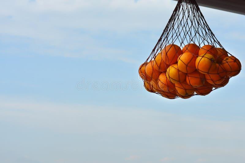 Fruits oranges dans le filet de achat avec le fond de ciel images libres de droits