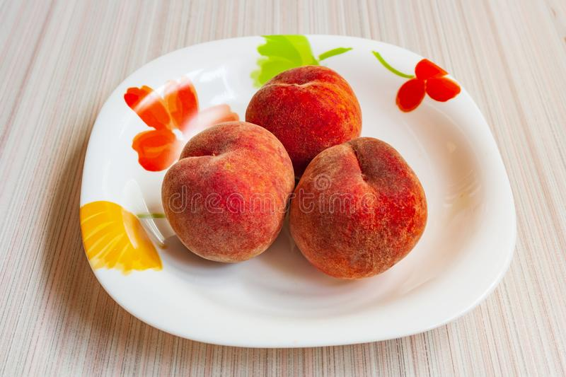 Ripe fruit peaches three pieces on a plate, in a Cup, in a bowl royalty free stock photo
