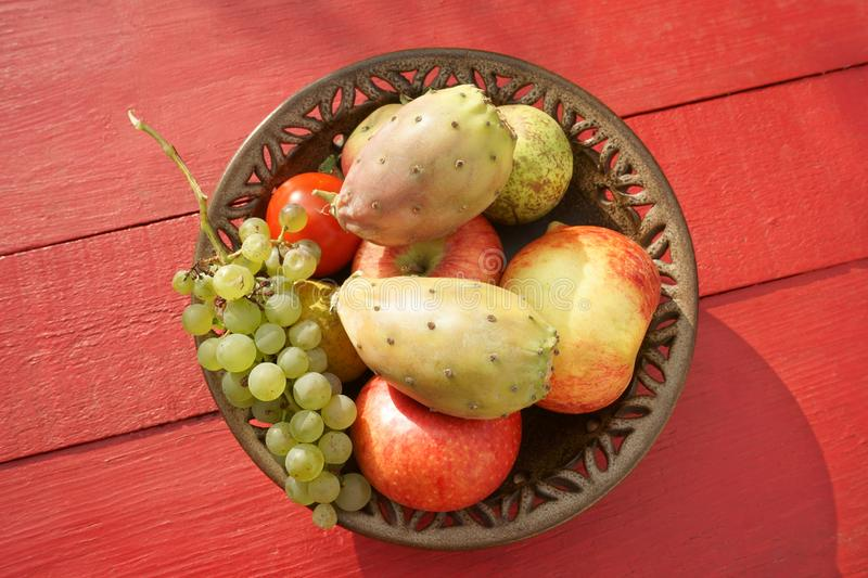 Fruits in plate on red table Cactus fruit Apples Tabletop royalty free stock photography