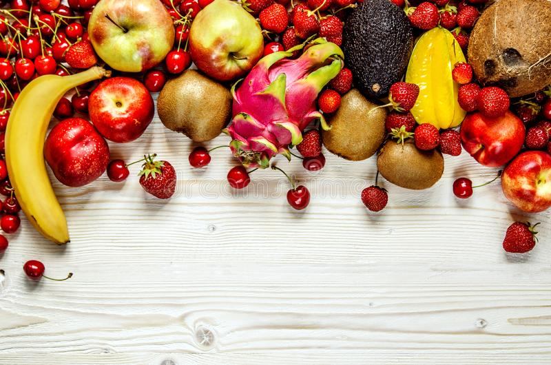 Fruits of cherry, strawberry, banana, avocado, carom, coconut, peach, apple and dragon fruit lie on a white wooden surface. stock photography