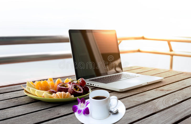 Fruits salad and cup of coffee and flower with computer laptop. And sunlight stock photography