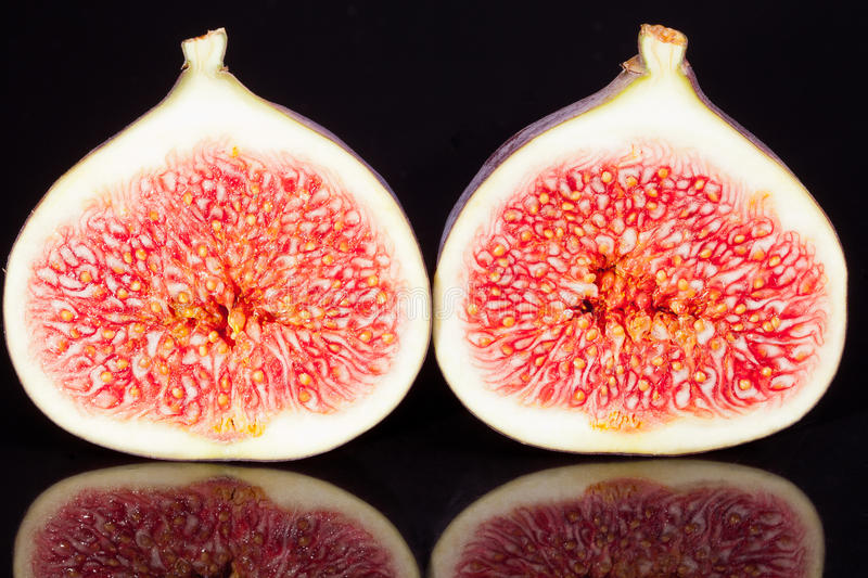 Fruits of sectioned fresh figs on black background stock photography