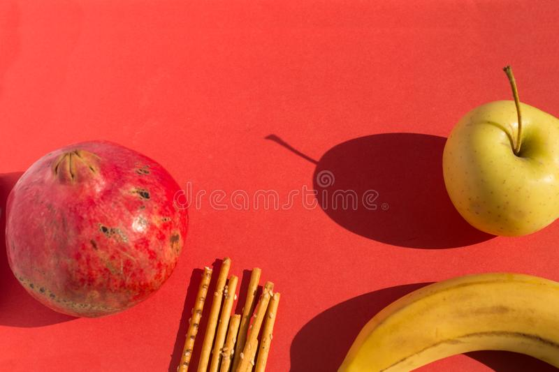 Fruits set: red pomegranate, Golden apple, fresh banana and salty sticks on red background. royalty free stock image