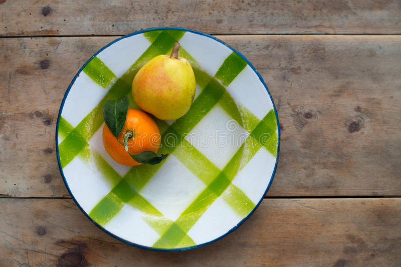 Fruits tangerine and pear in vintage porcelain dish plate. On retro wood table stock photo