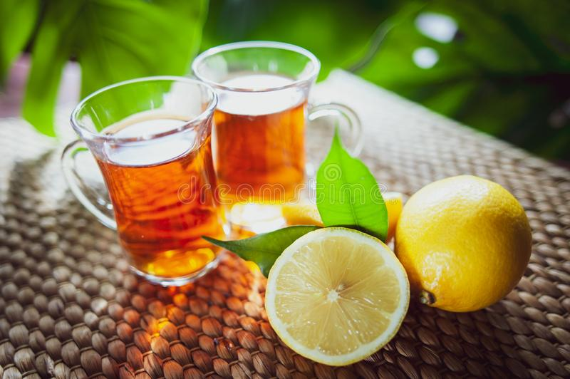 Fruits tea made from Limon , organic tea , fresh limon fruits whole and half on a natural tropical background stock image