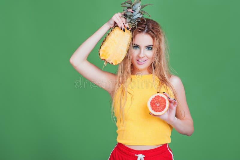 Fruits tropicaux savoureux ! Femme sexuelle attirante dans des vêtements lumineux de sport tenant le pamplemousse et l'ananas ju photos libres de droits