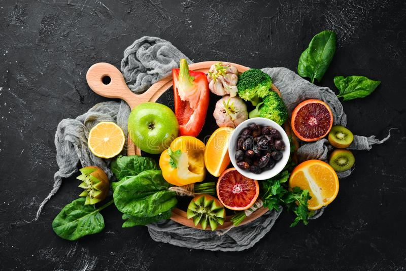 Fruits and vegetables that contain vitamin C: Orange, lemon, apple, roses, garlic, broccoli, apple, kiwi, spinach. Top view. On a black stone background stock photo
