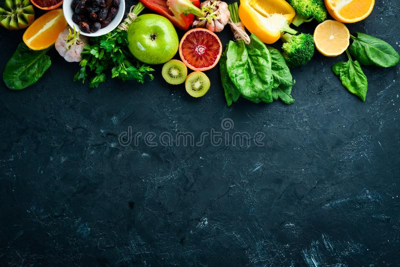 Fruits and vegetables that contain vitamin C: Orange, lemon, apple, roses, garlic, broccoli, apple, kiwi, spinach. Top view. On a black stone background stock images