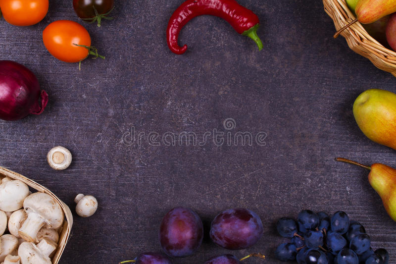 Fruits and vegetables on dark wooden background royalty free stock photography