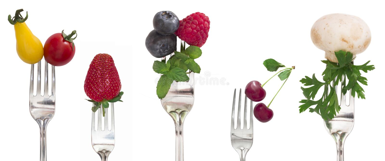 Fruits and vegetables on the forks stock image