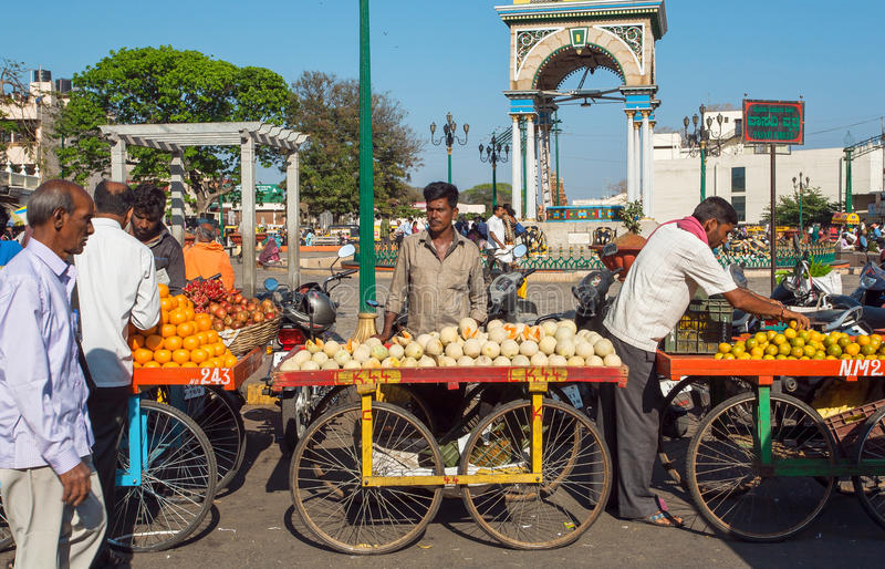 Fruits and vegetables traders selling melons and mandarins on busy street market royalty free stock photo