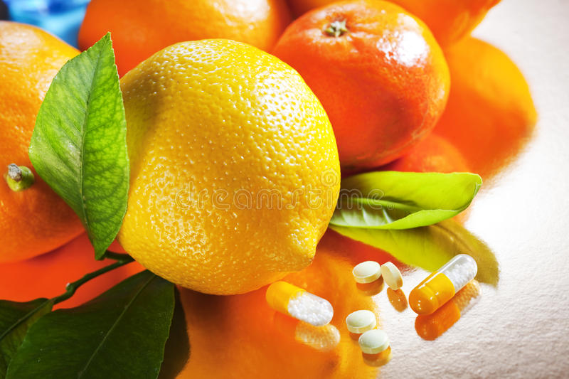 Fruits and vitamines. Fruits and vitamin C peels on silver background stock image