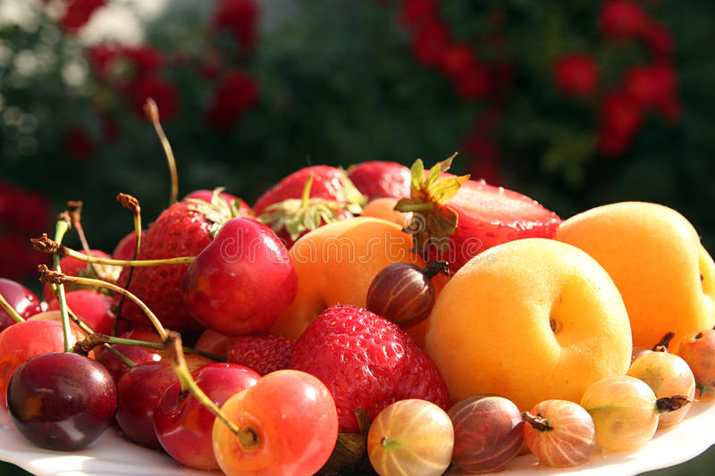 Fruits on white plate. Against flowers background stock photography