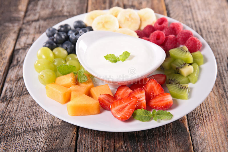 Fruits and yogurt dip. On wood stock images