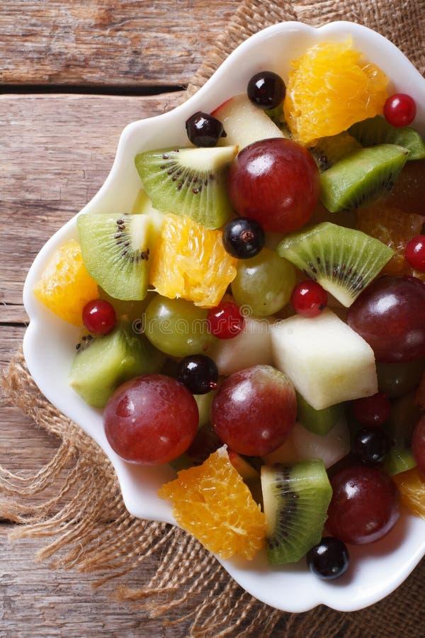 Fruitsalade in de witte verticale hoogste mening van het plaatclose-up, plattelander stock fotografie
