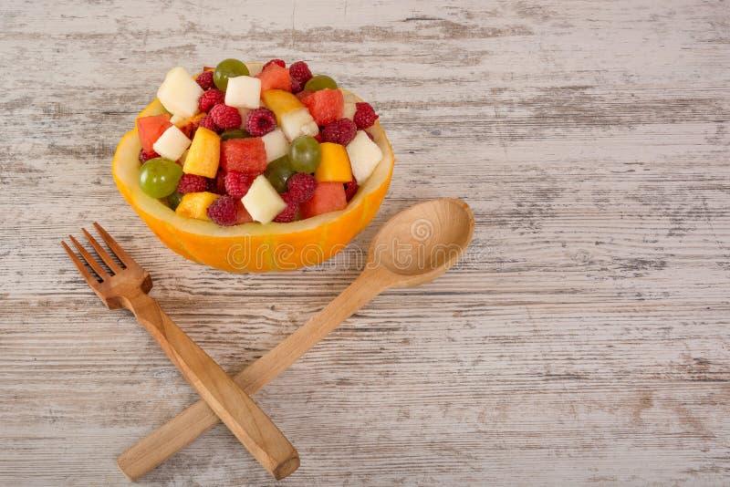 Fruitsalade in een meloensalantitsa, een houten lepel en een vork stock foto