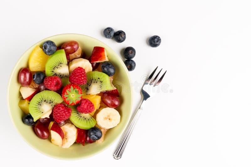 Fruitsalade in Groene Kom, bosbessen en vork op witte Lijst, Hoogste Weergeven De ruimte van het exemplaar royalty-vrije stock afbeeldingen