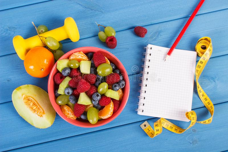 Fruitsalade, meetlint met domoren en blocnote voor het schrijven van nota's, gezond levensstijl en voedingsconcept stock foto's