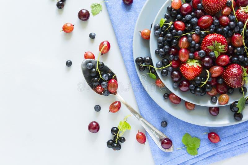 Fruitsalade met aardbei, bosbes, kers, kruisbes en zwarte bes op houten grijze achtergrond Vlak leg Hoogste mening royalty-vrije stock foto's
