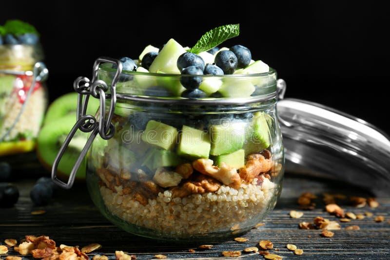 Fruitsalade met quinoa in glaskruik die wordt gediend stock foto's