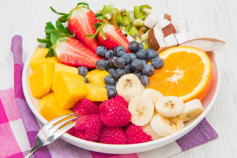 Fruitsalade met verse bessen, sinaasappel, kokosnoot, mango, en gesneden van banaan stock afbeelding