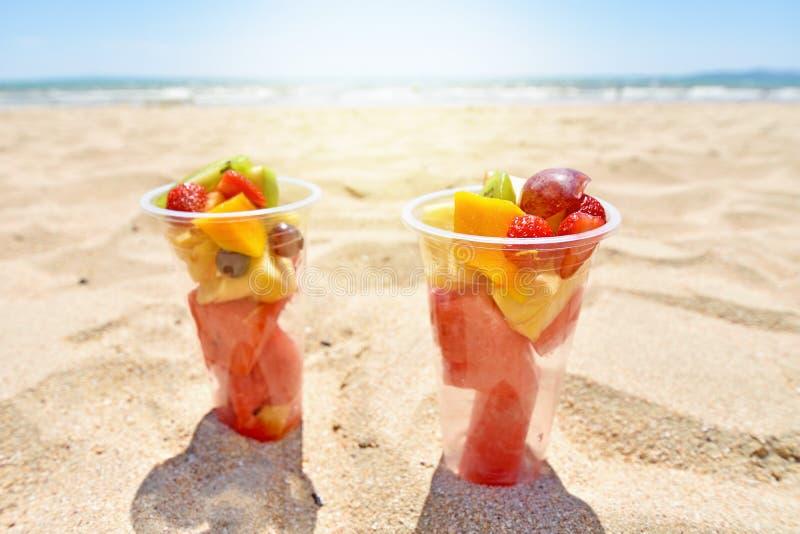 Fruitsalade in plastic koppen op de zomerstrand royalty-vrije stock afbeelding
