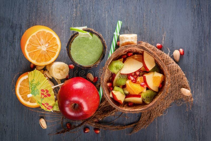 Fruitsalade van appelen, bananen, sinaasappel en granaatappel in de helft van een kokosnoot en verse groene smoothies van groente stock foto