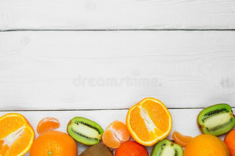 Fruitsinaasappel, mandarijn en kiwifruit op witte houten uitstekende achtergrond royalty-vrije stock foto's