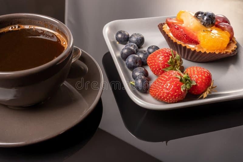 Fruittartlets op een houten plaat en een kop van koffie op de lijst, fruit gebakken shell, fruit cupcake met bessen royalty-vrije stock foto's