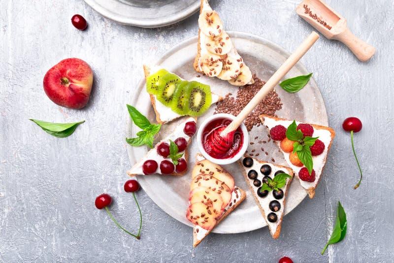 Fruittoost op grijze achtergrond Het gezonde ontbijt Schone eten Het op dieet zijn concept De plakken van het korrelbrood met roo royalty-vrije stock foto's
