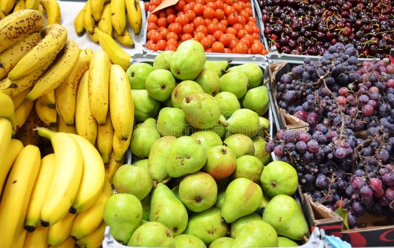 Fruittribune bij de markt met de druiven en de kersen van bananenperen stock afbeelding