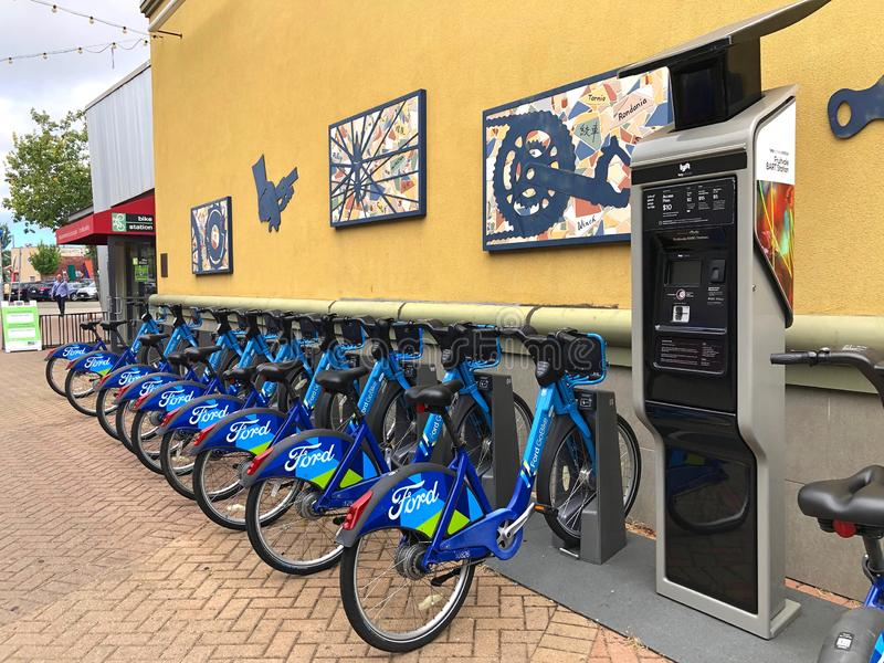 Bicycle rental station at Fruitvale Bart in Oakland, California. Fruitvale, CA - June 26, 2019: Blue Go Ford shared bikes lined up in the at Fruitvale BART royalty free stock photo