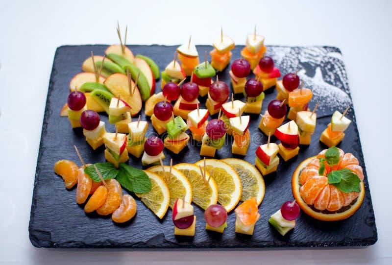 Fruitvleespennen - de verse appel, de kiwi, de citroenplakken, de mandarijn, de druiven en de kaas, dienden op zwart steendienbla royalty-vrije stock foto's