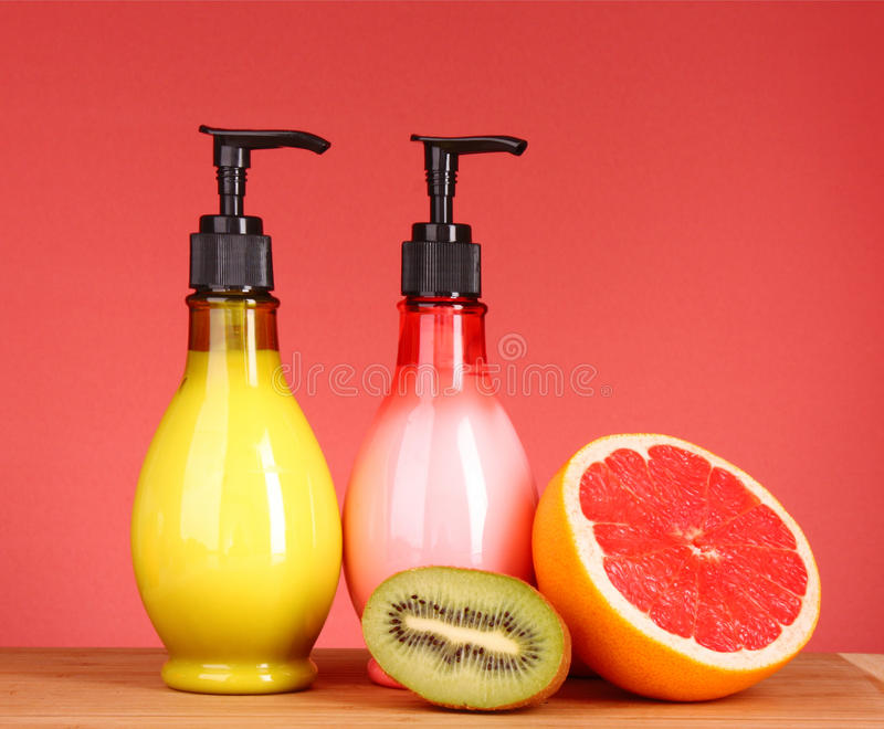 Fruity body lotion,. Grapefruit and kiwi fruit on a red background stock photo