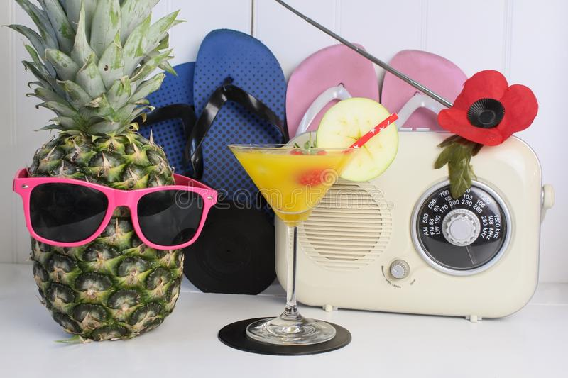 Fruity cocktail beach party arrangement. Fruity cocktail next to a pineapple with sunglasses, flip flops and a radio stock image
