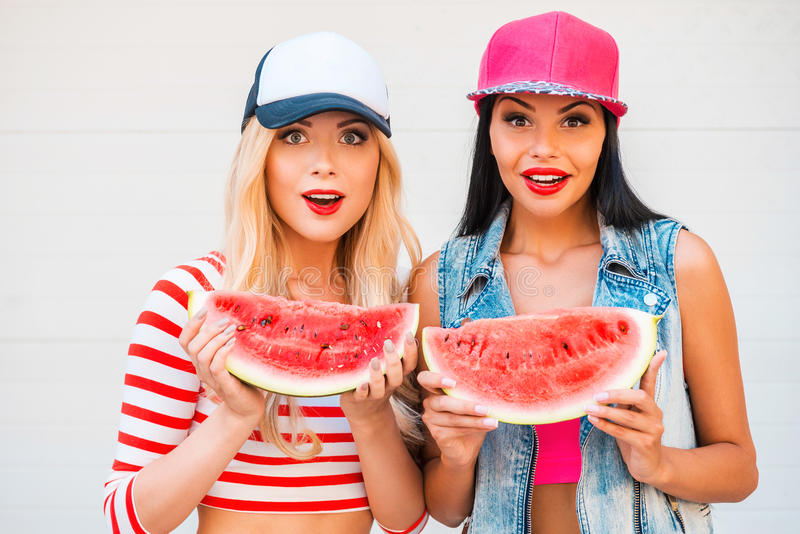 Fruity fun. Two surprised young women holding slices of watermelon and staring at camera while standing outdoors royalty free stock photos