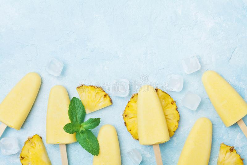 Fruity homemade ice cream or popsicles from pineapple top view. Summer refreshing food. stock photo