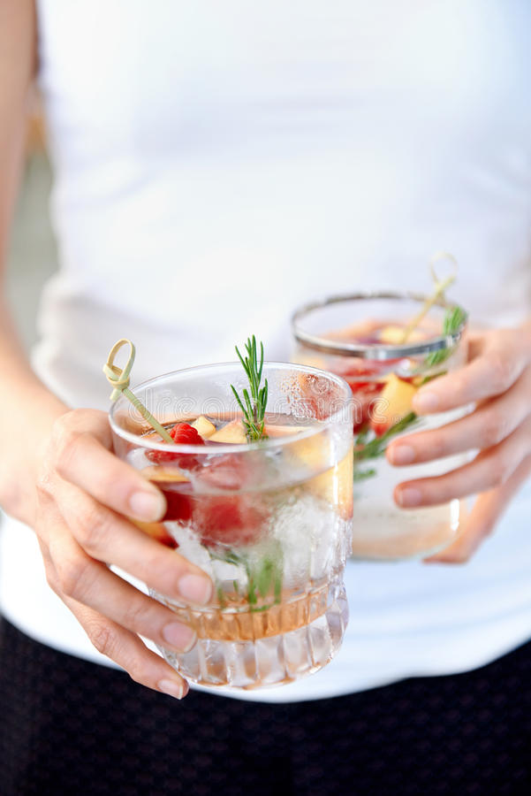 Fruity refreshments. Anonymous woman holding two fruity cocktails with fresh fruit raspberry and rosemary garnish royalty free stock photography