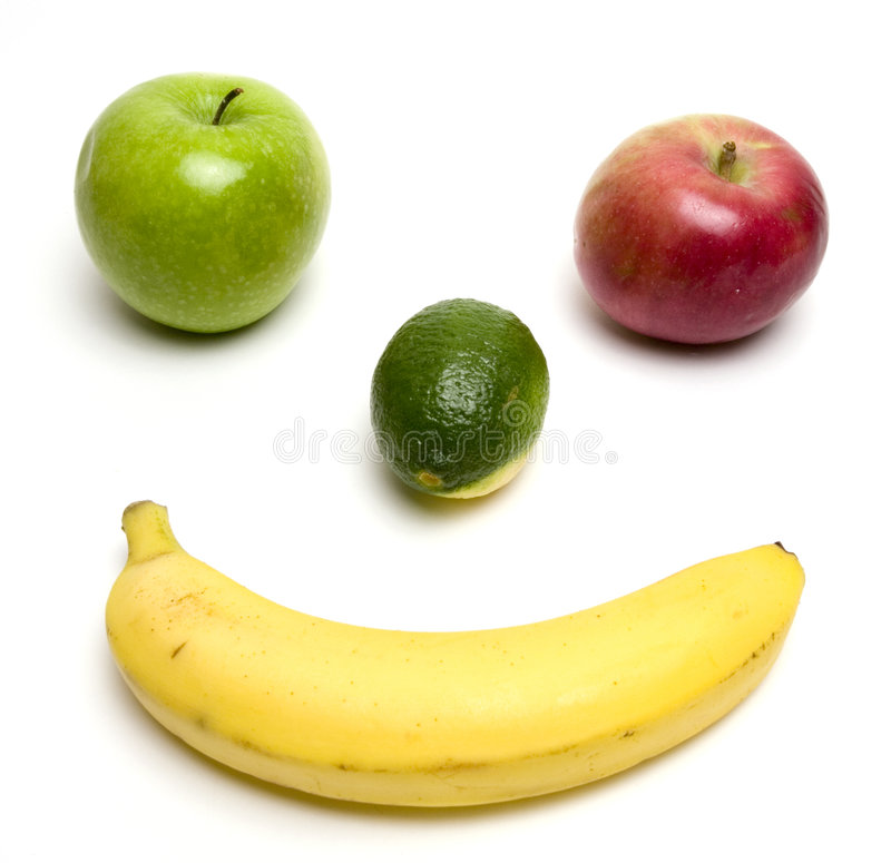 Fruity smile. Apples, banana and lime constructing a smiley face stock photo