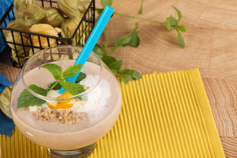 Fruity smoothie w deserowym szkle z błękitną słomą na żółtym tle Koktajle z wysuszonymi morelami, lody i fotografia stock