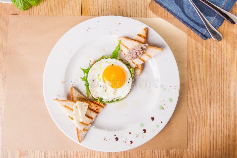 Frukost för bästa sikt med stekte ägg, rostade bröd och köttpate på den vita plattan på den tjänade som trätabellen Selektiv foku arkivbilder