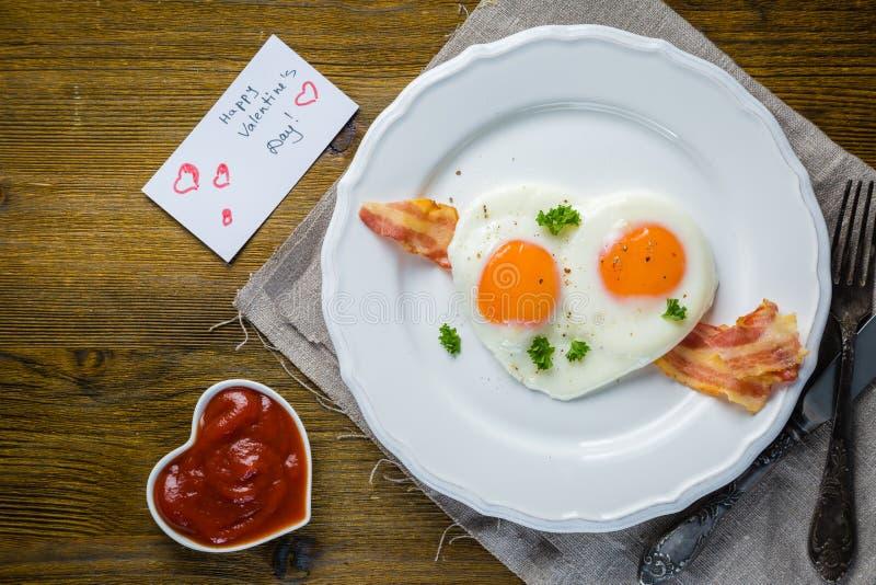 Frukost för dag för valentin` s - ägg, bacon, ketchup arkivbilder